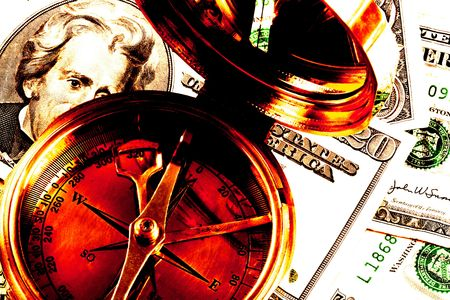 atop: Navigating Financial Waters - a high contast image of an old brass compass atop US currency Stock Photo