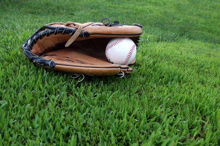 guante beisbol: Guantes de cuero y pelota de b�isbol en el c�sped del outfield Foto de archivo