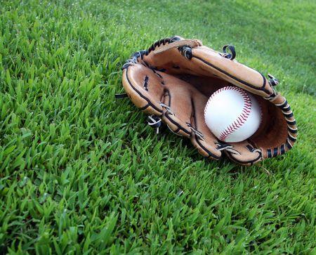 guante beisbol: Cuero guante de b�isbol y bal�n en el c�sped del outfield
