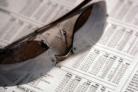 Sunglasses atop the business section of a newspaper - Financial Decisions Stock Photo - 592190