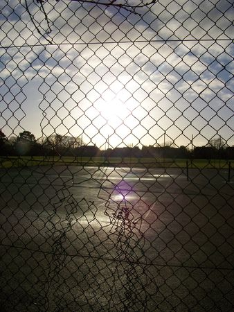 the sun shining down, reflecting on the tennis court, behind the fence Stock Photo - 785193