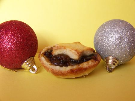 mince pie: a home made mince pie and 2 christmas baubles on yellow background