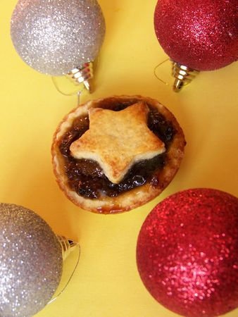 mince pie: a home made mince pie and 4 christmas baubles on yellow background  Stock Photo