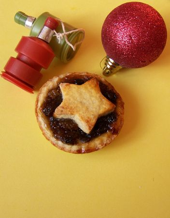 poppers: a red bauble a mince pie & 2 party poppers on yellow background  Stock Photo