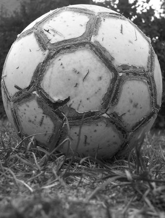 tatty: a tatty football on the grass, in black & white