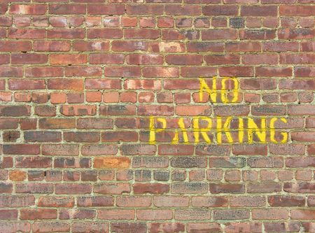 ordinance: NO PARKING painted in yellow on a brick wall Stock Photo