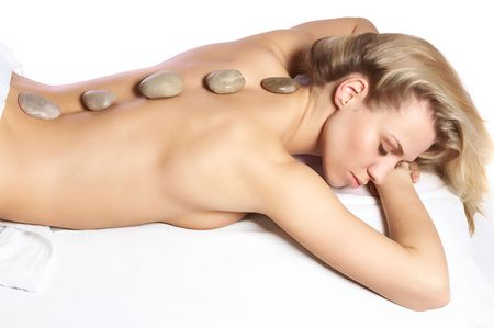 Sleeping cute girl getting a stone massage in a spa