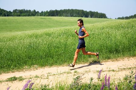 Running along a meadow the man Stock Photo