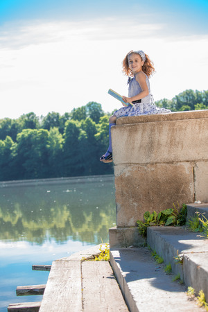 Little girl in white dress reading a book by the lake photo