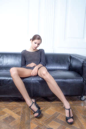 beautiful brunette with long legs sitting on the couch