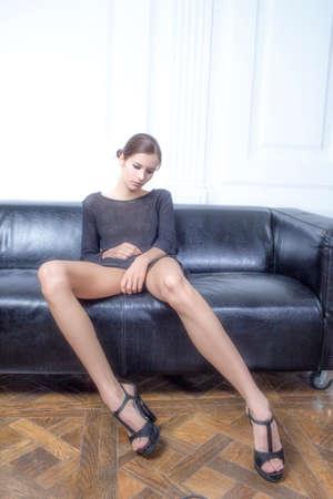 pies sexis: hermosa morena de piernas largas que se sienta en el sofá