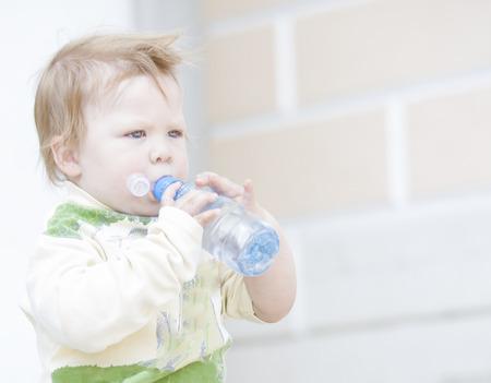 Little boy drinking water from a plastic bottle photo
