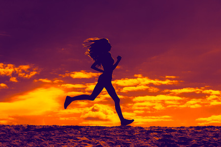 Silhouette of a girl running on the background of clouds the effect of film photo