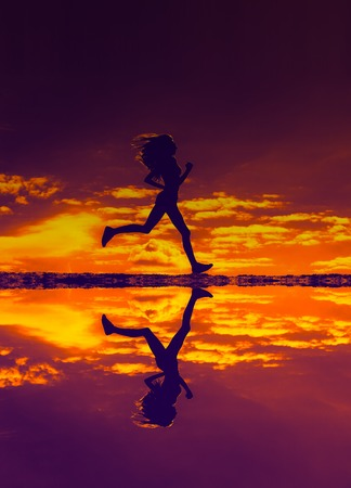 country lifestyle: Silhouette sport girl running and reflected in the water