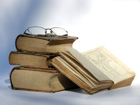 Old style vintage books with glasses on the top of them