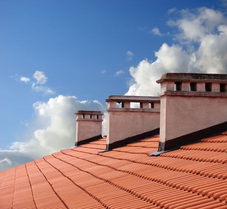 roof top: Chimneys on roof of red tiles with blue sky and clouds.                                Stock Photo