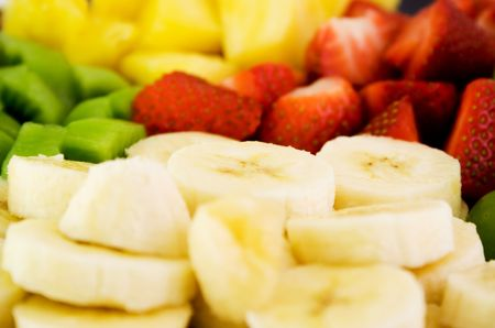 Fruit plate with bananas,strawberries,kiwis and pineapple with soft deep of field photo
