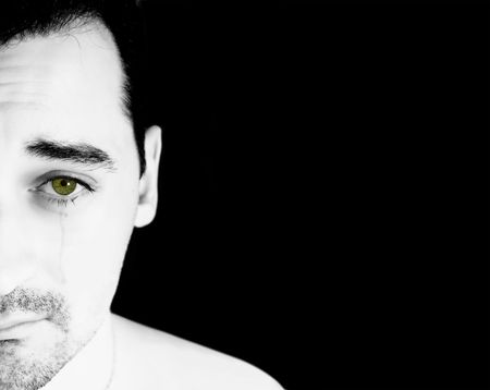 fear: A white man with green eye crying isolated on a black blackground Stock Photo