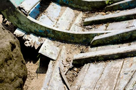 Old broken boat with a rock into it photo