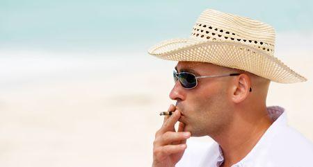 Man smoking cigarette on a beautiful beach photo