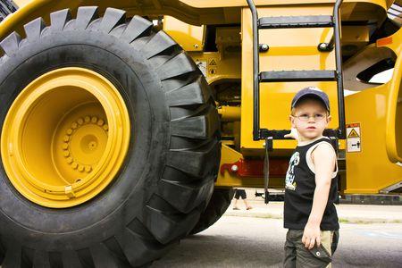 big wheel: Little boy ready to work on a construction truck