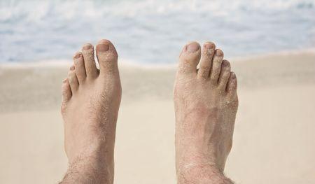 Pair of mans feet on the beach photo