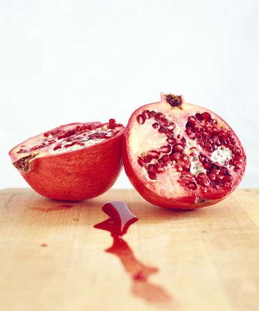 centers: pomegranates cut in half with pomegrante seeds showing and juice on a cutting board