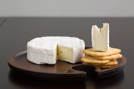 cheese plate: Brie with wedge cut out and butter crackers on a wooden cheese plate