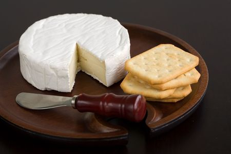 cheese plate: Brie and butter cracker on a wooden cheese plate with cheese knife