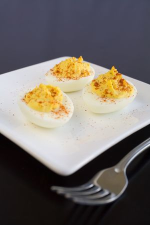 deviled eggs: Three deviled eggs with smoked paprika on a white plate