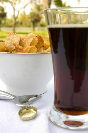 schwarzbier: Pilsner Glas gef�llt mit dunklem Bier und Chips als Snack. Sonnigen Tag im Caf�.