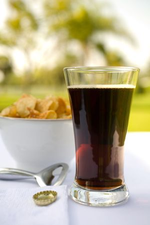 bottle cap opener: Pilsner Glass filled with dark beer and potato chips as a snack. Sunny day at the cafe. Stock Photo