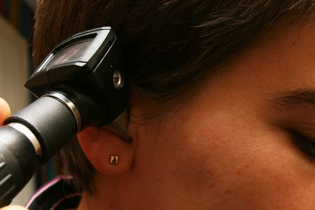 people listening: Medical equipment being used to check womans hearing