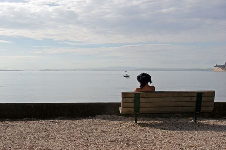 pained: Man sitting on a bench overlooking the beach enjoying the view Stock Photo
