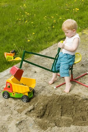 dumptruck: Little boy working construction in his sandpit