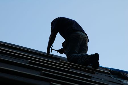 man on roof installing tar paper Stock Photo