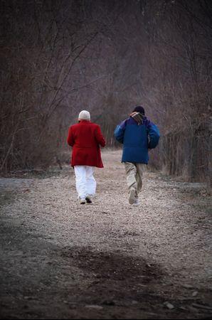 mature couple jogging on path photo
