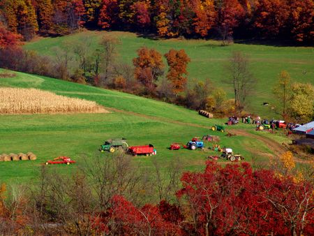 farmland landscape with truck tractors and hay bales