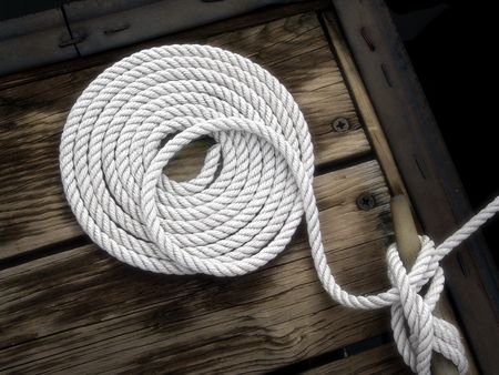 white boat rope tied to dock photo