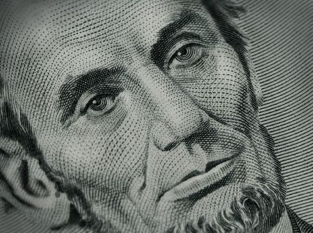 close up of Abraham Lincoln on five dollar bill Stock Photo