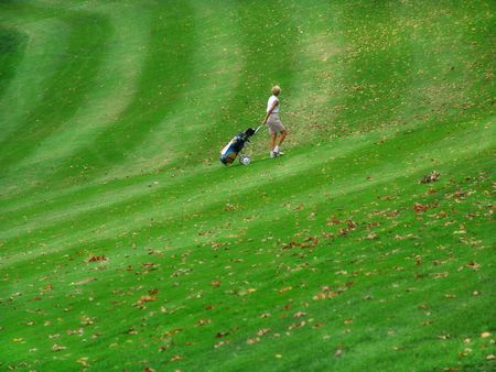 woman on golf course pulling bag