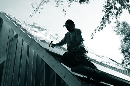 man on roof installing tarpaper Stock Photo