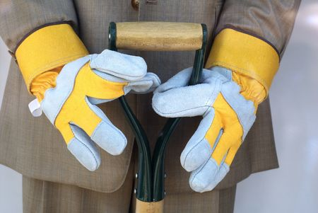 rushed: male mannequin holding shovel in business suit with garden gloves - busy life metaphor