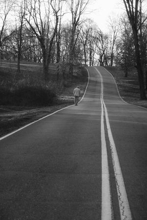 black and white of man walking on country road photo