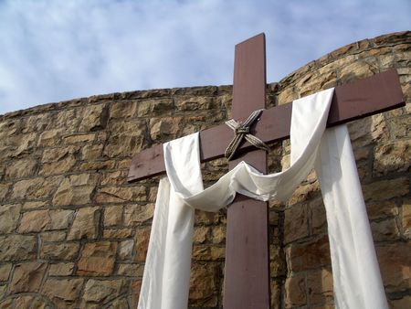 Christian cross with cloth in front of church