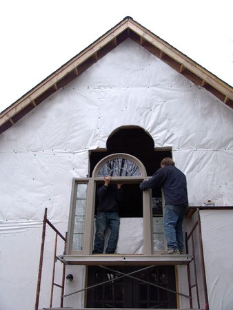 men installing window in new house photo