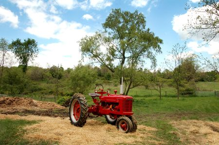 antique tractor sitting in country landscape