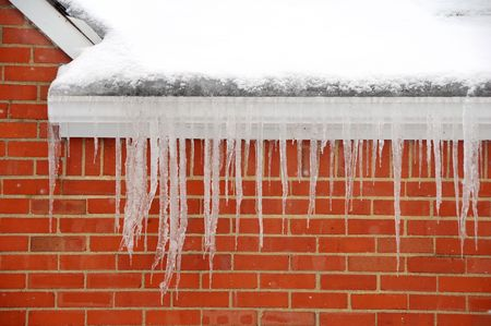 icicles hanging on side of house in winter Stock Photo