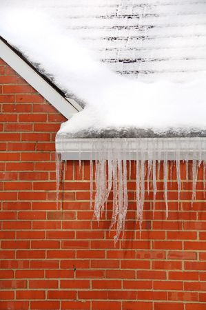 icicle spikes hanging on side of house in winter Stock Photo