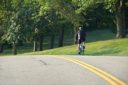 man riding bicycle on street with trees Stock Photo